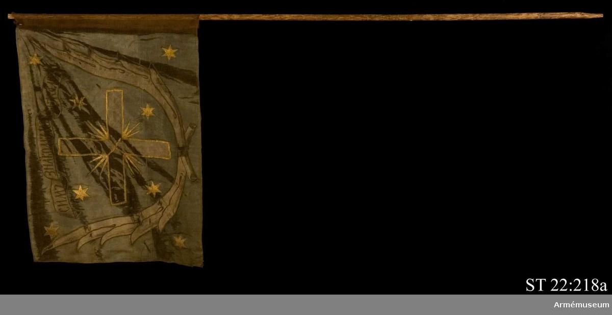 """Duk av grön sidendamast med infälld och målad dekor bestående av ett kors omgärdat av palmblad i vit sidendamast. I ett textband rysk text betydande """"I detta tecken ska du segra"""". Strumpa av rött ylle. Slät stång."""