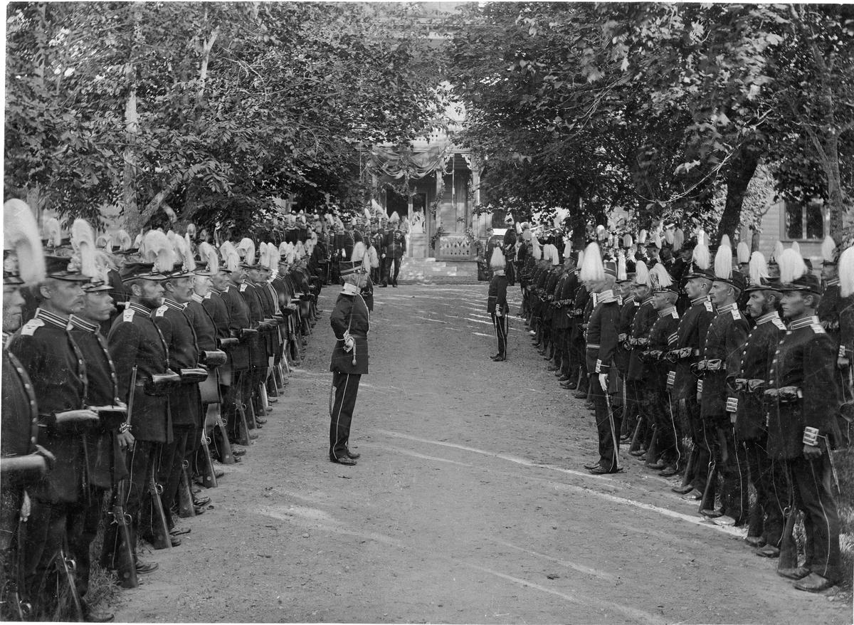 Livkompaniet vid Livregementet till fot (I 3) paraderar vid ingången till officerarnas matpaviljong den 29/8 1897, då officerskåren gav middag för sin avgående chef, överste Johan Lilliehöök. I bakgrunden spelar musikkåren.