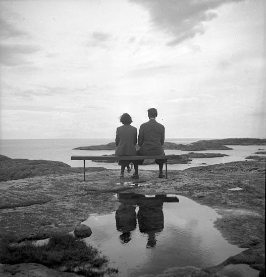 Kvinna och man sitter på en bänk och skådar ut över havet
