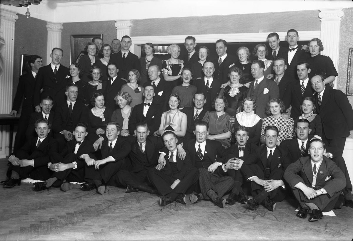 Festklädda kvinnor och män i en samlingslokal.