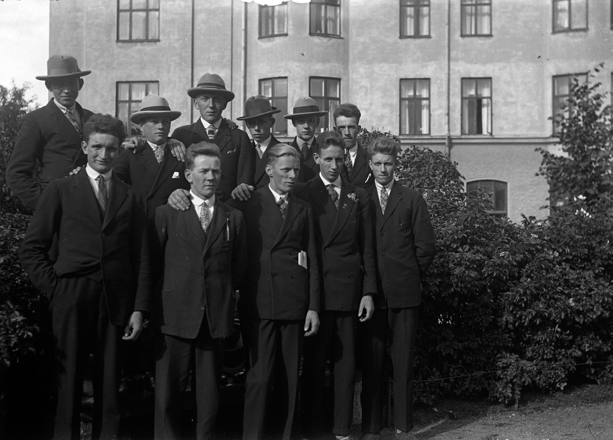 Elva män står i två rader framför en buskplantering och med ett bostadshus i bakgrunden.