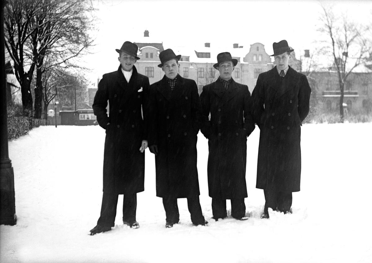 Fyra män i rock och hatt står uppställda för fotografering på Pilgatan i Jönköping en snöig vinterdag. Till höger ligger Västra torget och i bakgrunden syns träd och bostadshus i sten.