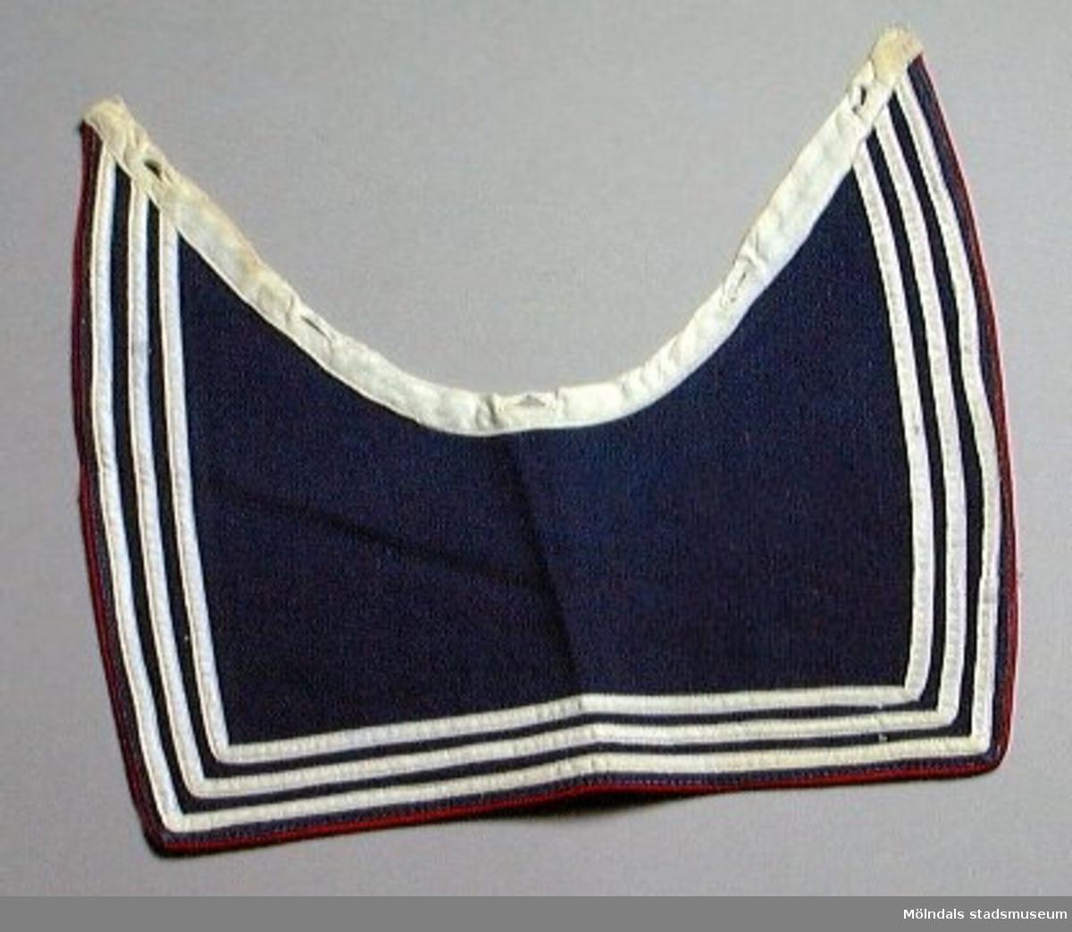 Blå maskinsydd barnkrage med tre rader påsydda vita band i kanten och rött kantband. Fem knapphål.