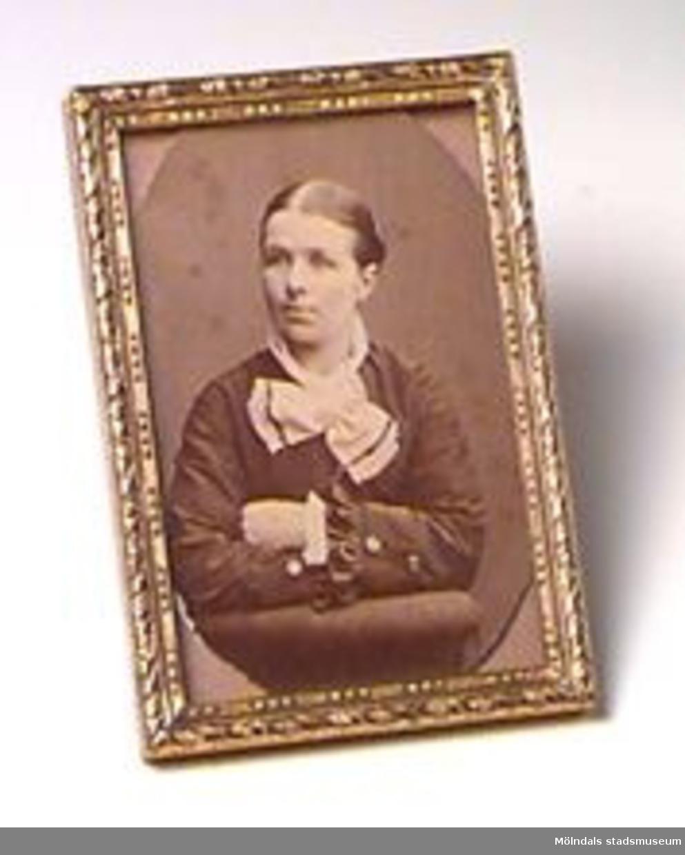 Ett porträttfoto med ram i mässing. Det ovan angivna måttet beskriver fotots mått. Mässingramen har måtten; H: 93 mm. B: 64 mm. Tj: 7 mm.Avporträtterad person är Josefina K Eriksson i  Våmmedal.Tidigare sakord: porträttfoto med ram.