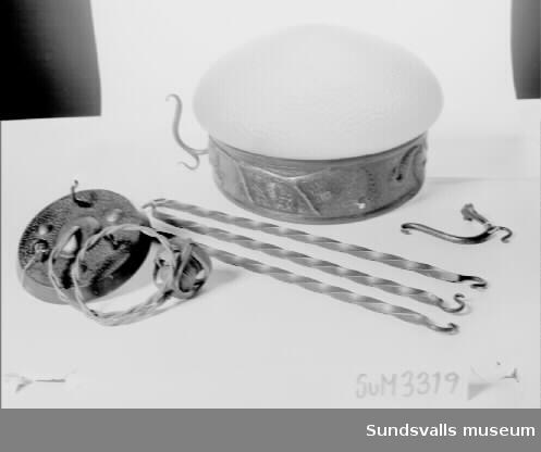 Taklampa i sex delar. Lampans kupa bärs upp av tre vridna stänger, 46 cm långa, med krokar. Kupans metalldel är ett brett band med relief föreställande ekorrar sittande på ekgrenar. Vidhängande lapp med texten 'Mobergs'.