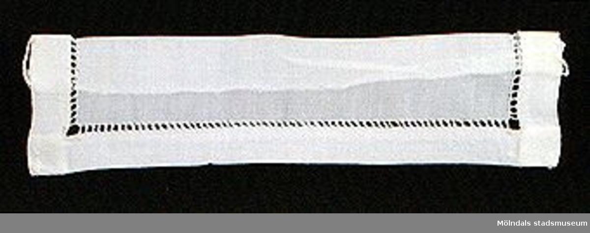 12 par vita lösmanschetter använda tillsammans med långärmade plagg. En del märkta med nr 41. 02253_1 L: 160 mm B: 55 mm._2 L: 160 mm B: 45 mm._3 L: 170 mm B: 60mm. Ribbat tyg._4 L: 190 mm B: 55 mm. Ribbat tyg._5 L: 200 mm B: 50 mm. Hålsömsprydda._6 L: 165 mm B: 80 mm. Hålsömsprydda (ej stärkta, märkta 15)._7 L: 160 mm B: 80 mm. Hålsömsprydda._8 L: 200 mm B: 50 mm. Hålsömsprydda._9 L: 180 mm B: 50 mm. Öglemönstrad spets längs kanten._10 L: 170 mm B: 55 mm. Smal spets längs kanten._11 L: 160 mm B: 45 mm. Spets längs kanten._12 L: 165 mm B: 50 mm. Ögleartad spets längs kanten.Paren förvaras i en tom chokladask (Cloetta Bristol praliner). Dessa har använts av vårdarinna Karin Hasselberg på Stretered.