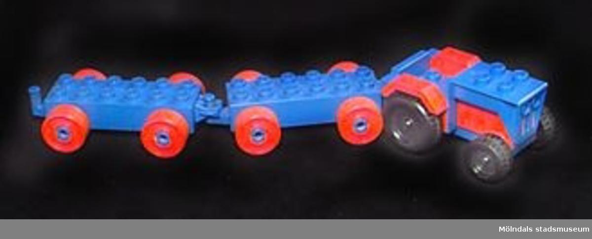 Leksakstraktor med två påkopplingsbara vagnar. Modulerna är specialdesignade delar av Duplosystemet, en förstorad variant av Legosystemet.MM 02361:1 traktor.MM 02361:2-3 släpvagnar.Katrinebergs daghem var ett kollektivt daghem.Gåva av Katrinebergs daghem.