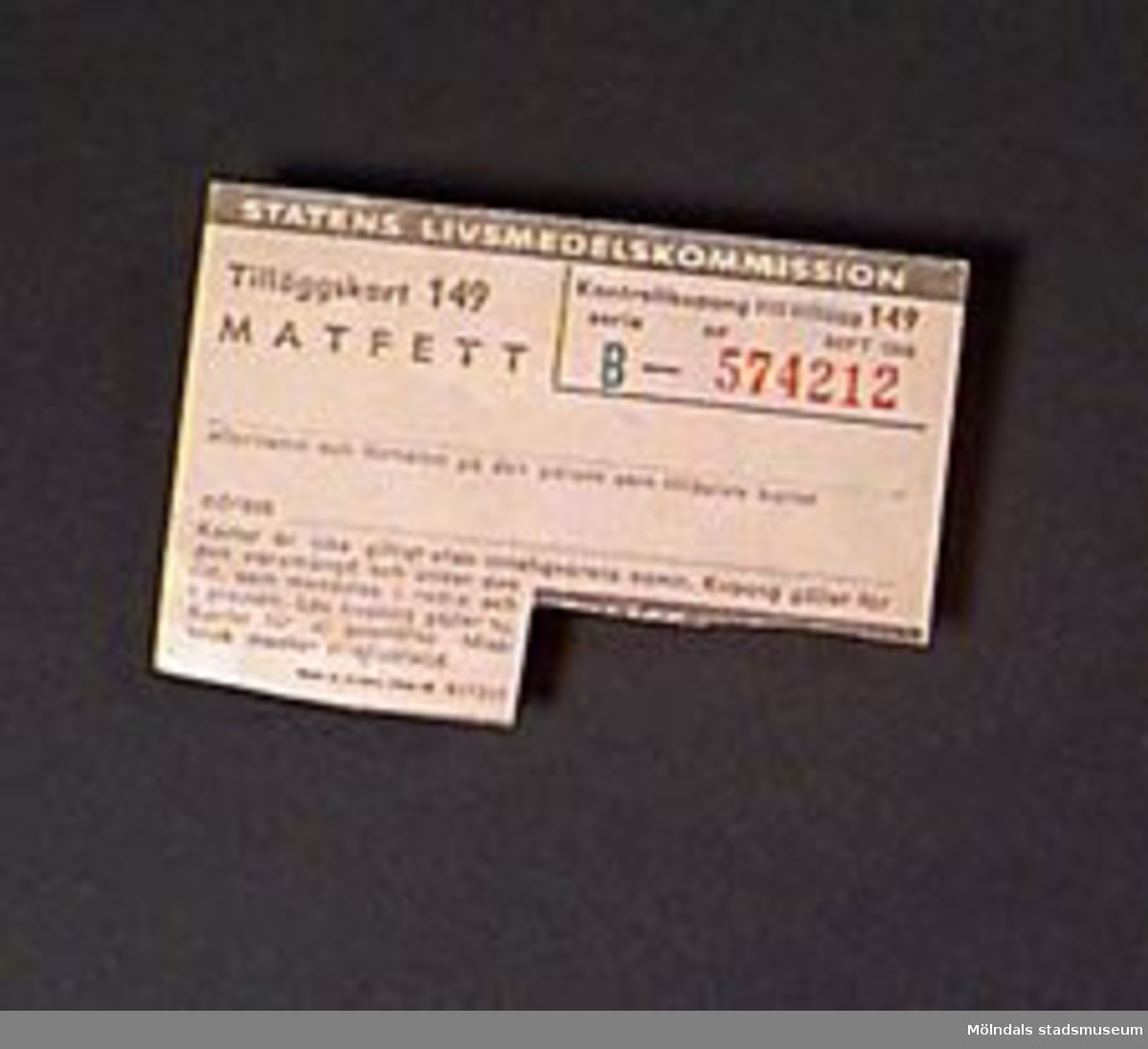 """Ransoneringskort för matfett. Kortet tillverkat för Statens livsmedelskommission. Gulbrunt papper med brun tryckt text. Serienummer tryckt i grönt och rött - """"B - 574212""""."""