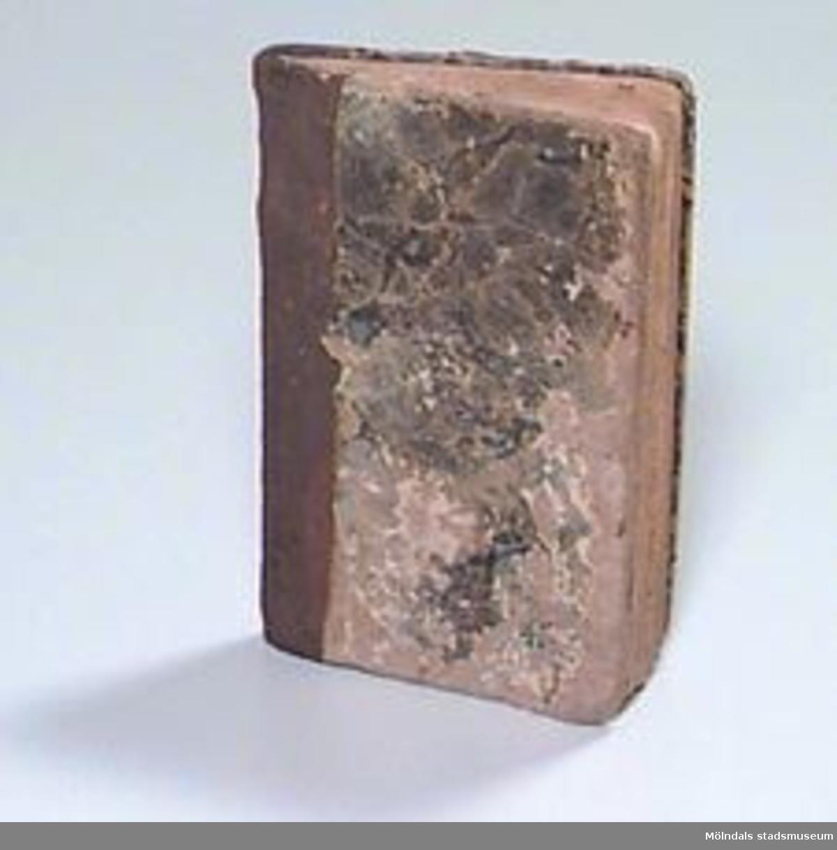 """""""Doct. Mårt. Luthers Lilla Cateches, med Förklaring af Doct. Ol. Swebilius. Ärke-Biskop."""" Pärmen klädd med dekorerat, gråblått papper, ryggen av läder. Skrivet med bläck på insidan av pärmen: """"Tillhörig MN(?) Johansson Smedlyckan --- 1870 --"""". (Initialerna mm svårlästa). På näst sista sidan skrivet med bläck: """"Hilda"""", """"MN Johansson"""", samt på bakre pärmens insida: """"Tillhörig MN Johansson Smedlyckan"""", """"Horn 1870 4/4""""."""