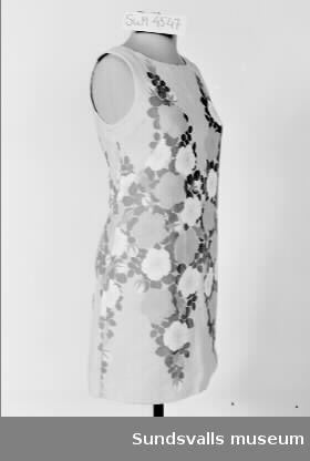 Ärmlös klänning i rak modell, rund hals och dragkedja i ryggen. Tyget är gult med blommönster i vitt, orange och grönt.