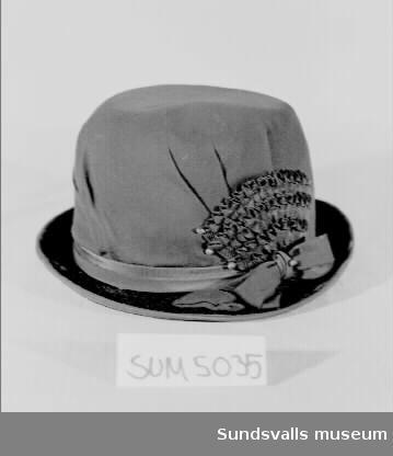 Svart hatt med smalt brätte, ca. 4 cm brett, och dekorationer i form av ripsband som lagts i täta veck och som kantar brättet, samt ett band och en rosett runt kullen. Fodrad. Inuti hatten finns en fastsydd etikett med texten 'Hilda Wickman, Styrmansgatan 10, STOCKHOLM'. På en lös papperslapp liggande i hatten står '117. A:s farmors hatt (sorg)'. Enligt anteckning från 1928.