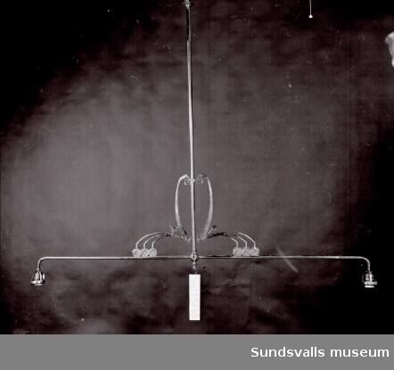 Armatur. Taklampa i metall med två vågräta armar fästa på en lodrät metallstång. Plats för en glödlampa längst ut på varje arm. Dekorationer där armarna möts.