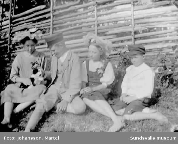 Två flickor i hatt samt två pojkar i keps vi gärdesgård. Kattunge i knät på en av flickorna. Se bild 0201,140.