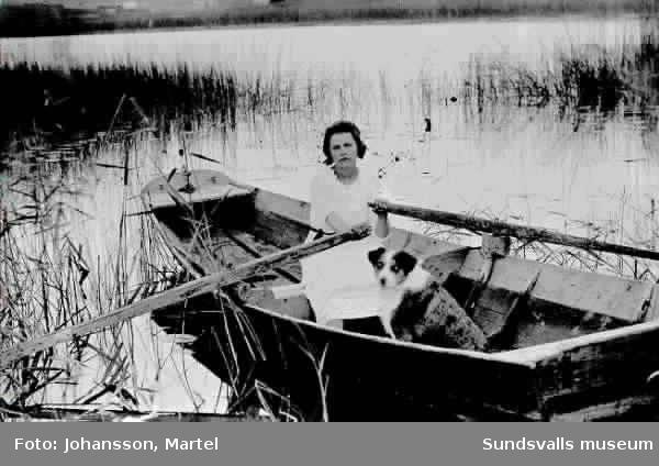 Porträtt av Ingeborg Muhr med hund, i ekan på sjön Vikarn.