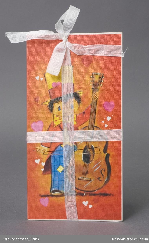 """2 st dubbla brevkort av papp med linnestruktur, ihopbundna med vitt sidenband.Framsidan; målning av pojke med cello, iklädd hög hatt och clownliknande kläder, omgiven av hjärtan. Detaljerna är präglade i upphöjd relief. På insidan finns plats för att skriva hälsningar, gratulationer eller liknande. Text på baksidan anger: """"Rust Craft, CC050, 470690, Copyright, Printed in England"""". Motivet är tryckt i England, men tillverkning har skett på Papyrus, Mölndal."""