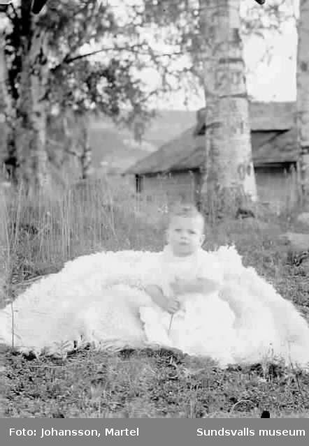 Porträtt.  Spädbarn som sitter i gräset på en filt.