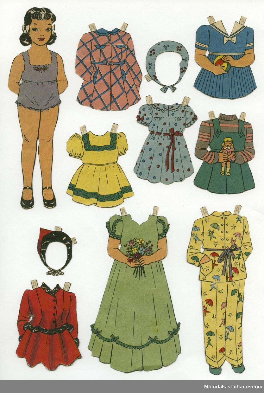 """Pappersdocka med kläder, urklippta ur Hemmets Veckotidning på 1950-talet. Docka och kläder är märkta """"Axi"""" på baksidan - dockans namn. Dockan föreställer en flicka med svart hår i tofsar, iklädd underkläder och skor. Garderoben består av fem små klänningar, varav en med sjalett, en långklänning, pyjamas, samt liten, röd dräkt med tillhörande hätta."""