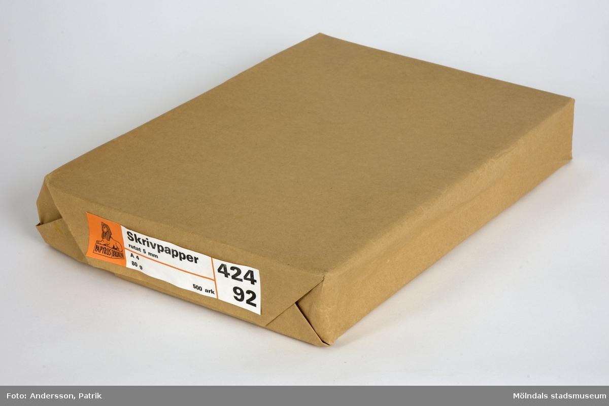 """500 st rutade skrivpapper som är förpackade med ett brunt omslagspapper från Papyrus i Mölndal.På sidan av förpackningen sitter en etikett med dessa uppgifter: """"Skrivpapper rutat 5 mm A 4 80 g 500 ark   424 92 """" + Papyrus loggan (en sfinx). Etiketten har färgerna orange och vit. Texten är svart.Storlek på förpackning:Längd: 301 mm Bredd:  214 mmDjup: 50 mm"""