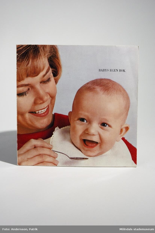 """Handbok - """"BABYS EGEN BOK"""", utgiven 1965 av Semper AB i samarbete med barnläkare och sjuksköterskor. Tryckeri: Stig Arbman AB.Bokens framsida är ett färgfotografi på en kvinna som matar en baby. Där står också bokens namn.Fotografiet fortsätter på bokens baksida. En del av baksidan är vit. Där framgår det att boken är:""""5:e upplagan. 500:e tusendetPris 3:50Stig Arbman AB/1965""""Handboken innehåller tips & råd kring barnets skötsel och mat. Längst bak i boken finns sidan: """"Mammas Dagbok"""", där hon kan fylla i:""""Du föddes denklockanDu vägde...och var...cm långDu döptes denDu fick mammas mjölk till Du varDu satt utan stöd vidoch reste Dig upp vid De första stegen tog Du när Du varDet första Du sa varoch då var DuDe första tänderna kom när Du varVaccinationerBarnsjukdomar""""MåttLängd: 199 mm, Bredd: 199 mm, Höjd: 3 mm"""
