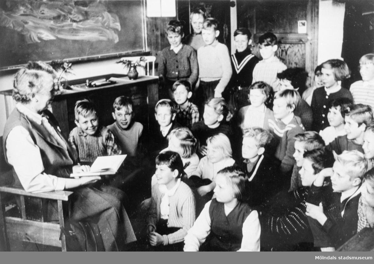 Läraren Elsa Spetz läser sagor för sin klass på Kvarnbyskolan (f.d. Centralskolan). Eleverna sitter och står på golvet framför fröken.