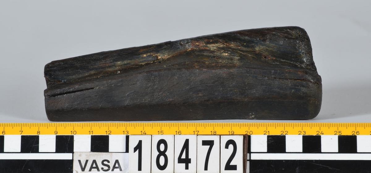 Ett ospecificerat verktygsskaft. Skaftet är åttkantigt samt avsmalnande i ena änden. I den smalare änden finns ett runt hål, troligtvis efter verktygsstålet. Skaftet är i gott skick, bortsett från en långsmal bit som är bortbruten vid skaftets smalare ände.  Text in English: A wooden handle. Octagonal shaft, tapering at one end with a round hole for the metal blade or shank. In good condition. A narrow splinter has broken off at the narrow end.