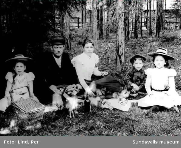 Alby 1898. Föräldrar samt tre barn,  dricker saft och äter bullar i skogsbrynet.
