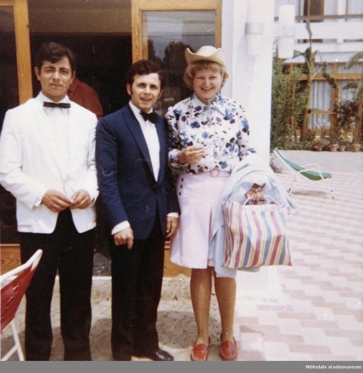 En kvinnlig elev, från Skolhemmet Stretered, som är på semester. 1970-tal. Med på bilden finns även restaurangpersonal från semesterorten.