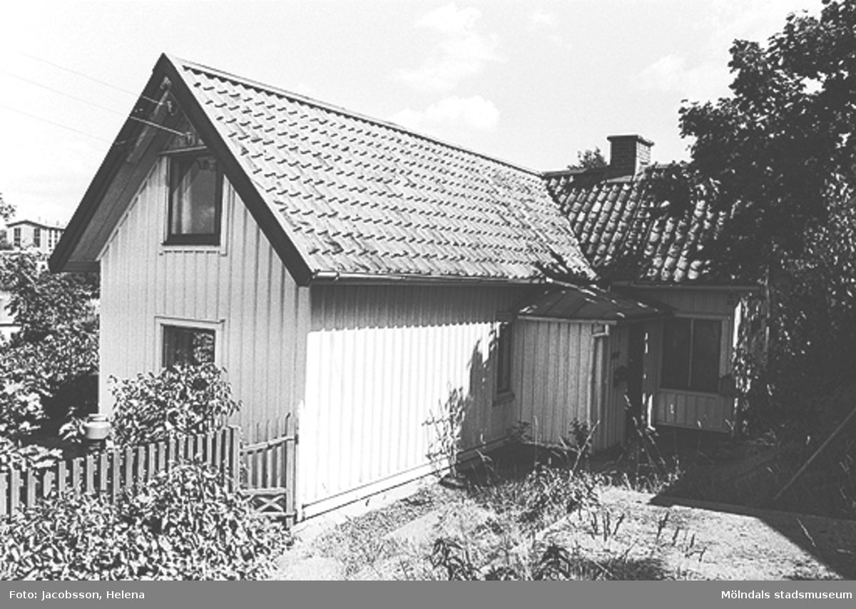 Exteriörbild av bostadshus med förstuga och uthus på Roten M 32 i Mölndals Kvarnby, 1972.