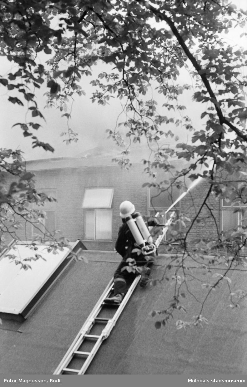 Soab-branden i Stora Götafors den 4 juni 1986. En brandman sprutar vatten från taket på andra sidan gatan.