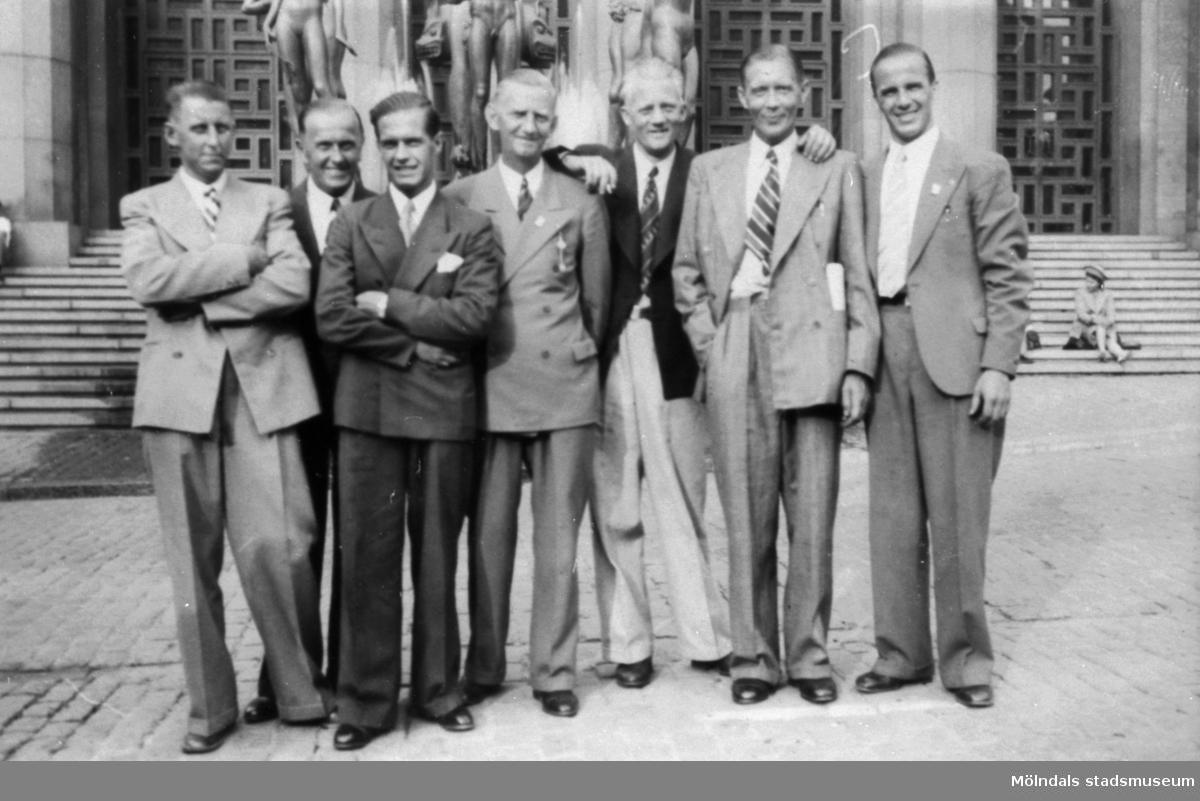 Sju kostymklädda män utanför Konserthuset i Stockholm 1931. Troligtvis representanter från Textilarbetareförbundet i Mölndal.