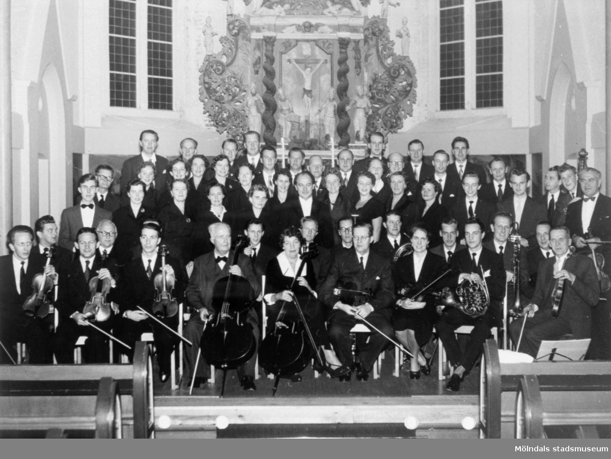 Mölndals körsällskap (dirigent: Lennart Hillman) sittande respektive stående framför altaret i Fässbergs kyrka, 1955. Okänd orkester.