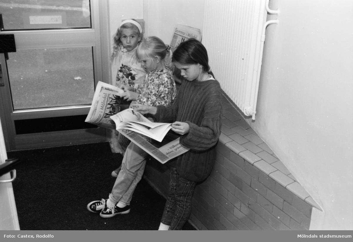 Tre flickor står lutade mot en entrévägg och läser tidningar. Utställningsvernissage av och om Katrinebergs daghem på Mölndals museum 1993-09-10.