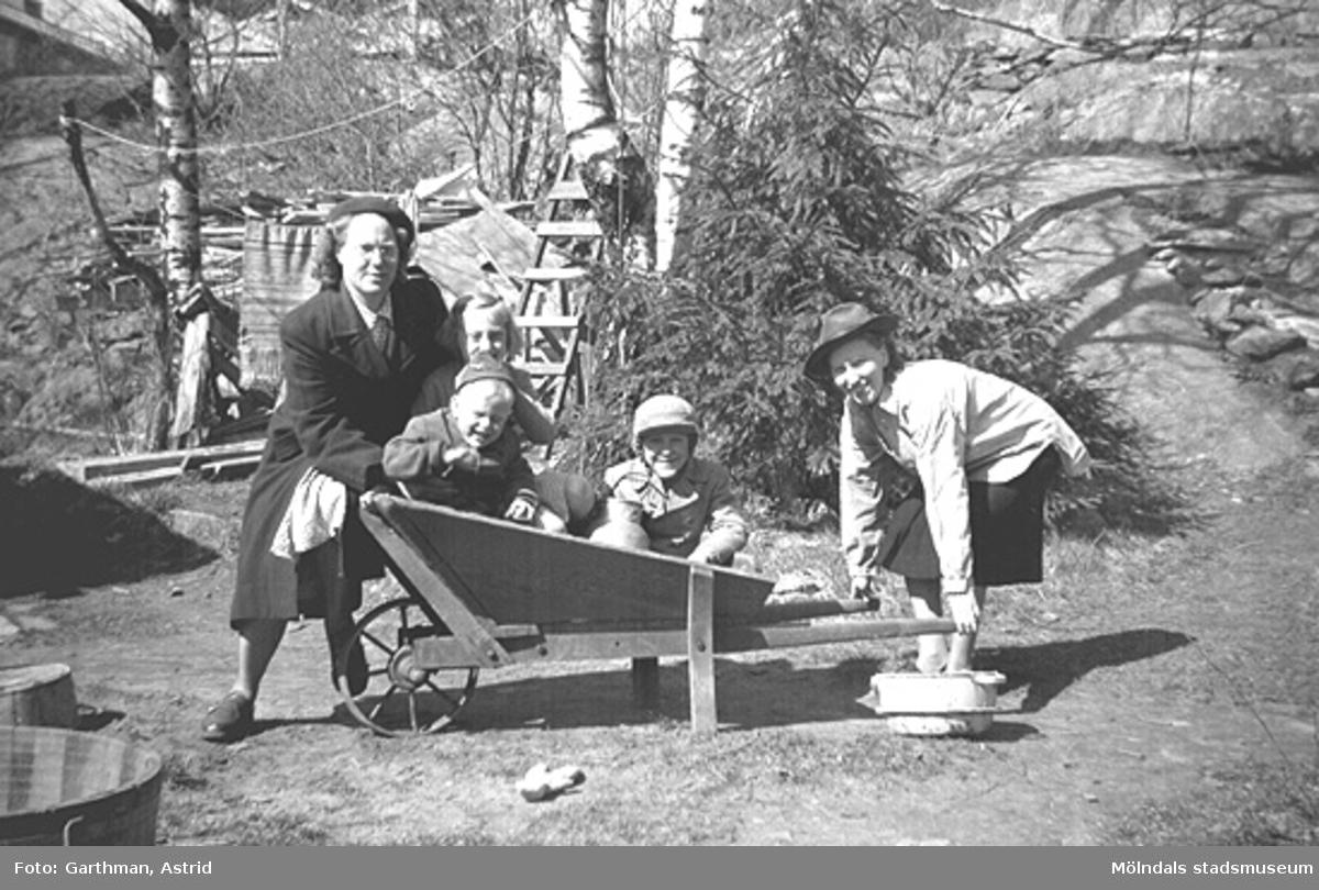 Besök hos Margit och Folke Larsson i Toltorpsdalen i början av 1950-talet. Från vänster: okänd kvinna från Norge med dottern Gurlie som sitter i skottkärran tillsammans med Alf Garthman och Per-Olof Larsson. Till höger: Margit Larsson f. Karlsson (moster till Alf Garthman).
