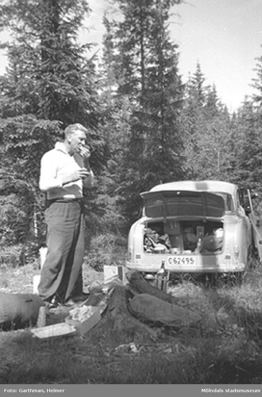 Elon Sävström (slöjdlärare på Sörgårdsskolan) och vännen Helmer Garthman (ej i bild) på väg till Norge för fiskesemester med Elons bil, en Borgward Isabella. Här är det paus i Värmland. 1960-tal. Skänkt av sonen Alf Garthman som arbetade många år på Mölndals stadsmuseum.