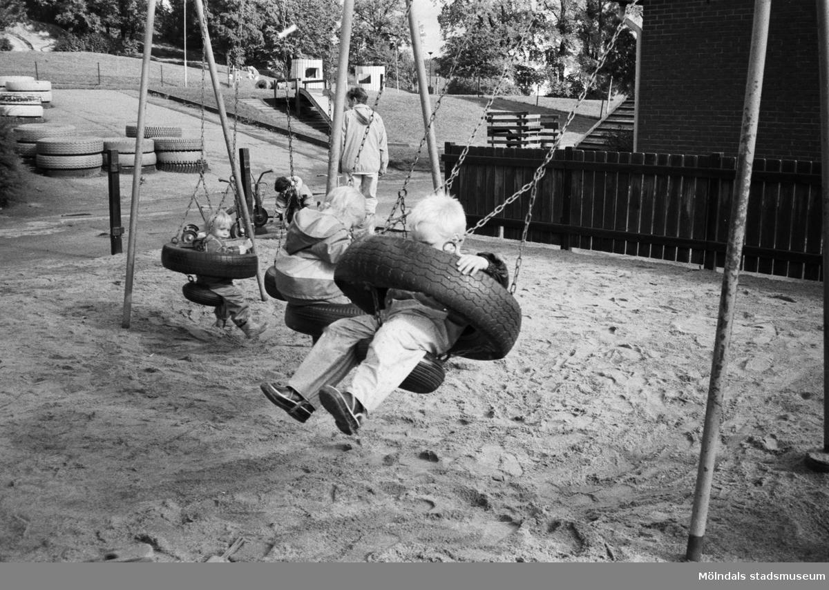Tre barn gungar i en gungställning som står i en stor sandlåda. I bakgrunden står en fröken med ett annat barn. Längre bort ser man stora däck man kan klättra i. Katrinebergs daghem, 1992.