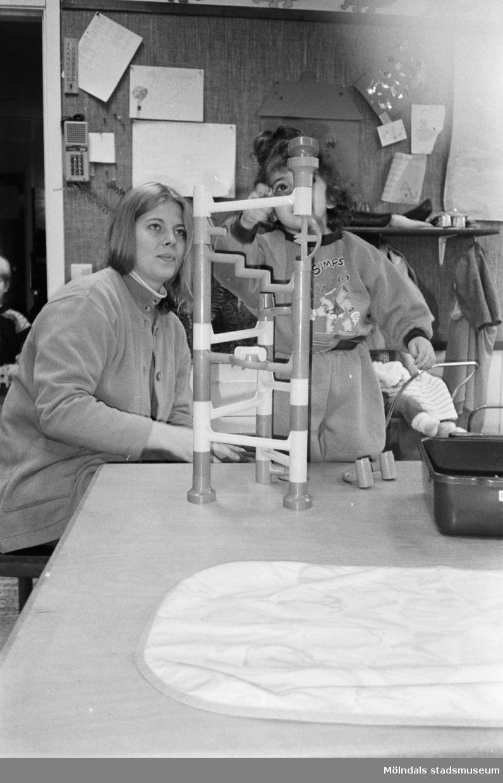 En förskollärare och ett barn tittar mycket intresserat på en ställning byggt av olikfärgade plastbitar/rör. Den är cirka 50 cm hög och står på bordet framför dem. I rummets bakgrund ser man en dockvagn och andra leksaker. En interntelefon sitter uppsatt på väggen. Katrinebergs daghem, 1992.