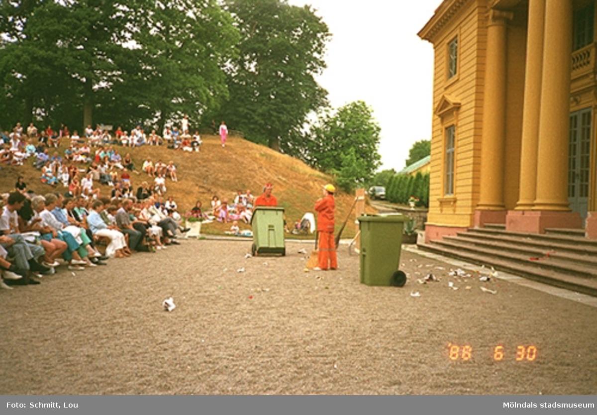 Människor som sitter och tittar på två personer i en teaterföreställning på Gunnebo slotts framsida. Skådespelarna är iklädda oranga overaller och har två gröna soptunnor som rekvisita. Man ser en del av det gula slottet till höger i bild.