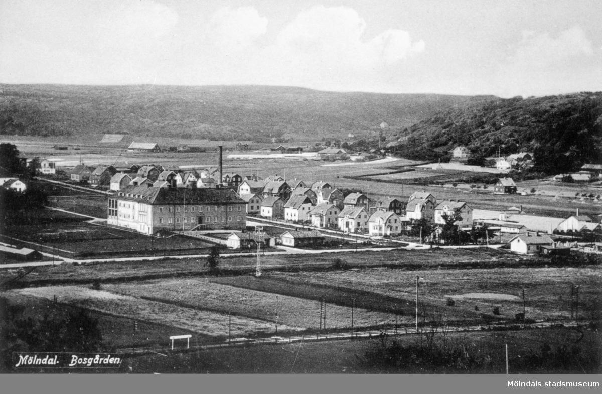 """Vykort """"Mölndal. Bosgården"""" med vy från sydost, 1920-tal. Man ser sjukhuset (stod klart 1924), Bosgården, östra delarna av Landstingsgatan och Bosgårdsgatan. I bakgrunden till höger ser man Västerberget och Toltorpsdalen som går mot Göteborg samt Safjället (närmast hitåt)."""
