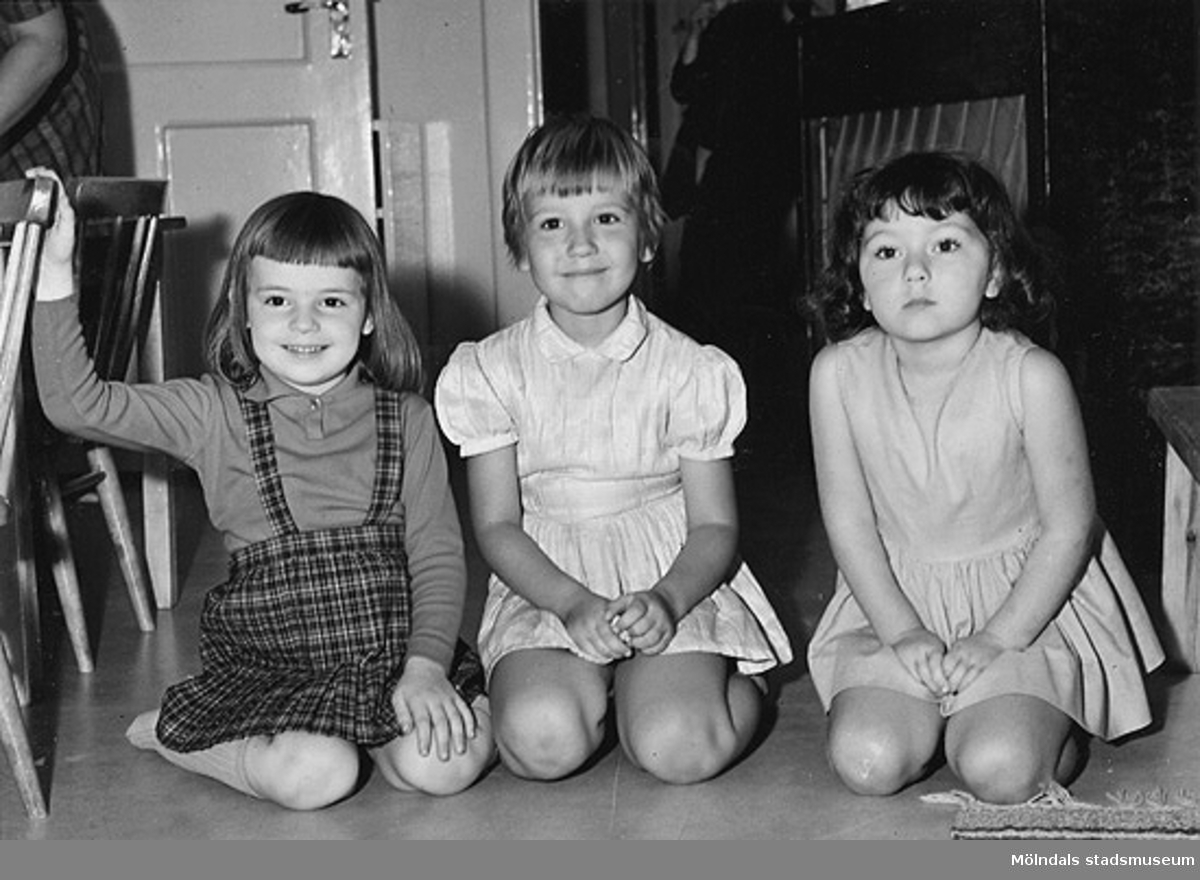 Tre flickor som sitter på golvet vid Holtermanska daghemmet 1953.