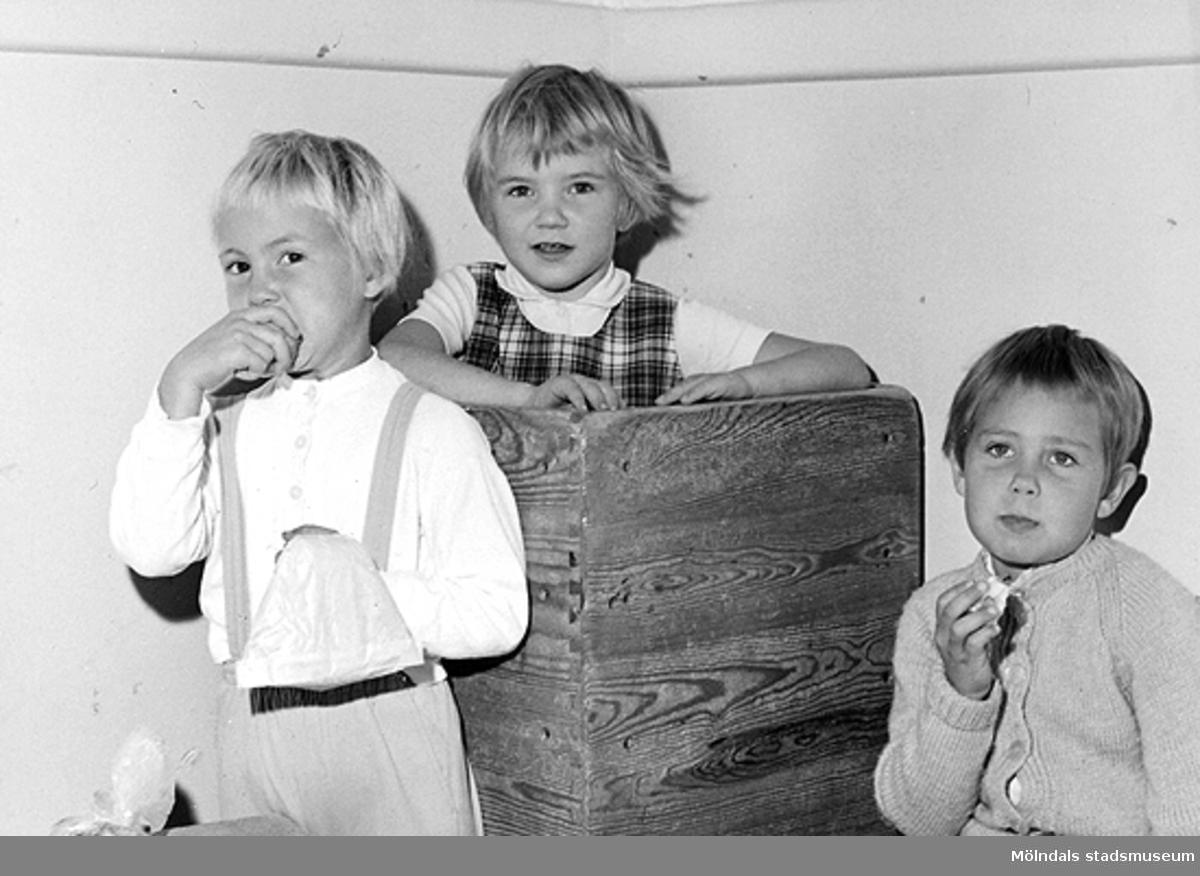 Tre barn som leker med stapelbara trälådor. Holtermanska daghemmet 1953.