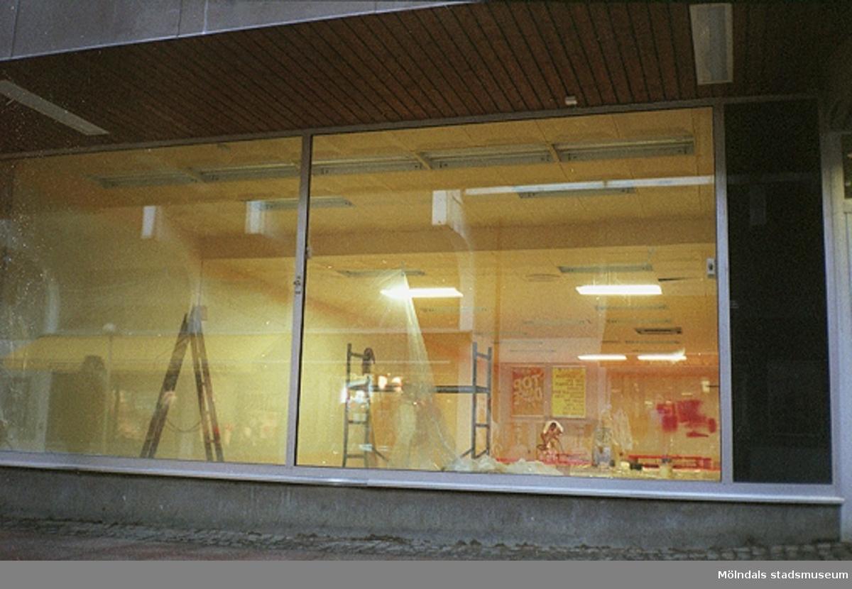 Vy genom en glasruta på en tom butikslokal som renoveras. Mölndalsbro i dag - ett skolpedagogiskt dokumentationsprojekt på Mölndals museum under oktober 1996. 1996_1227-1245 är gjorda av högstadieelever från Kvarnbyskolan 9D, grupp 6. Se även 1996_0913-0940.