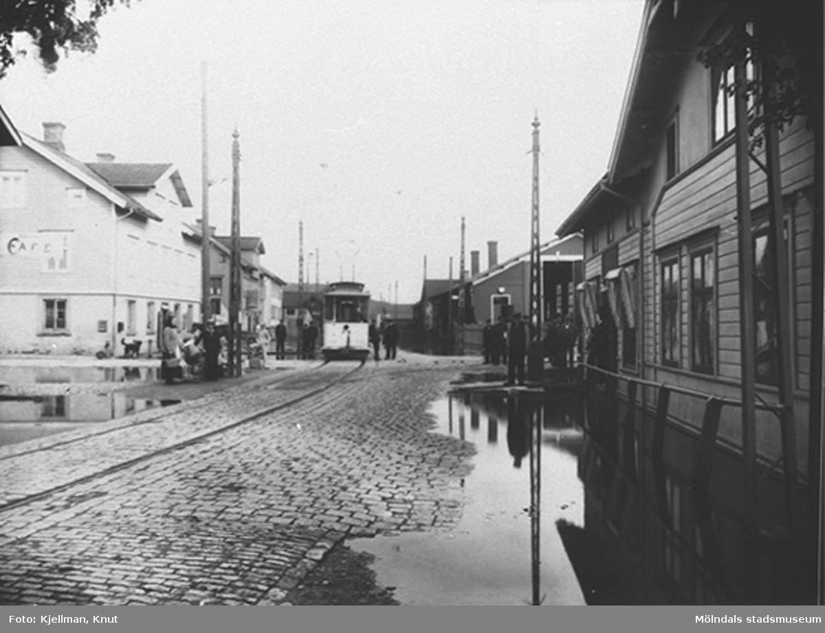 """Översvämning vid Mölndalsbro, 1907, sett söderifrån från Kungsbackavägen. 4:ans spårvagn är på ingående. Från vänster: Göteborgsvägen 1, 3 och 5. På andra sidan vägen: spårvagnshallarna och Hjertstrands hus (""""Bankhuset"""" på Kungsbackavägen 1)."""