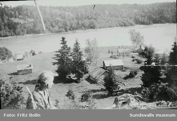 Fjärdbotten 1925. Norafjärden,  Ångermanälvens dalgång, vy.                                  Greta Bolin framför fäbodvallen i Fjärdbotten.