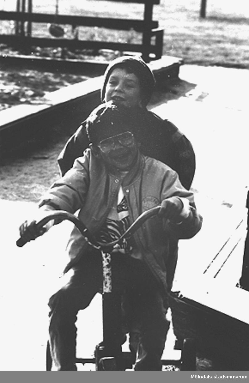 Främst sitter Jarmin Abdagalil och bakom honom sitter Andreas Carlsson. Bifrosts daghems lekplats, hösten 1987.