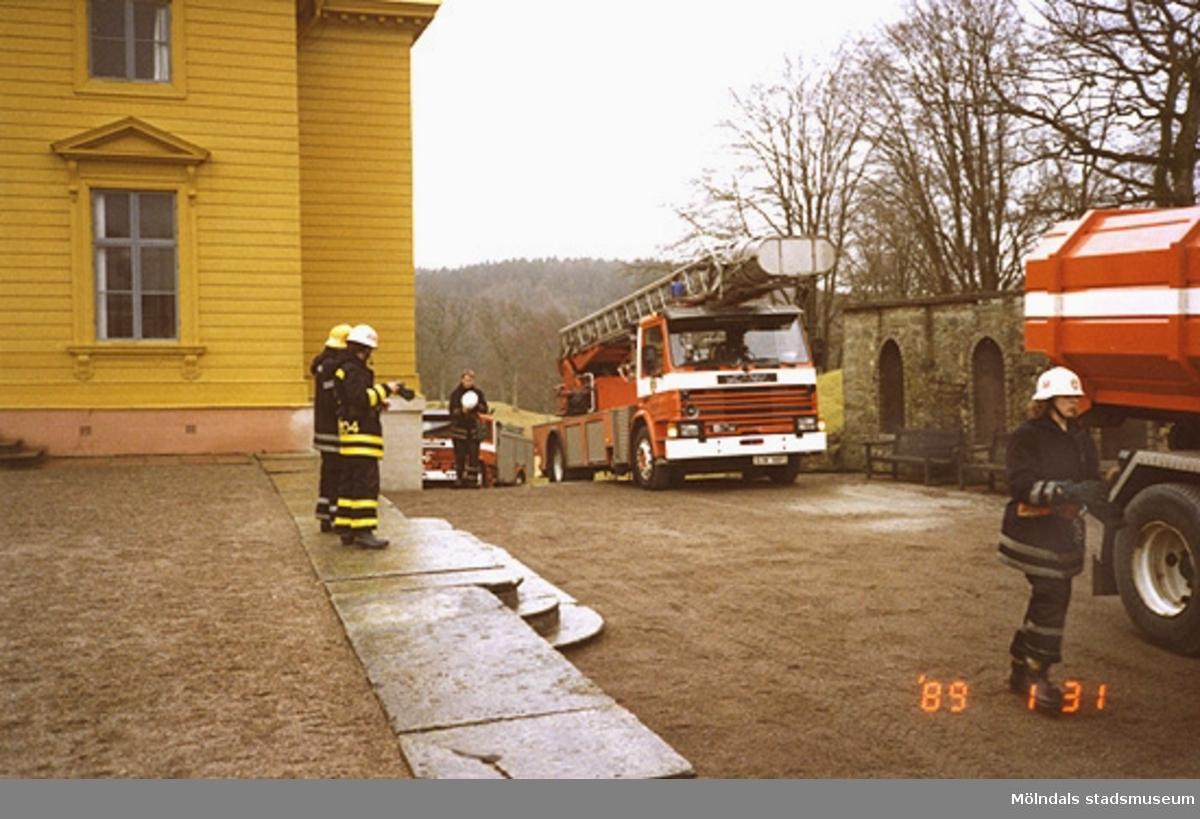 Tre brandbilar ståendes efter varandra utanför slottets västra sida. Även några brandmän står där.