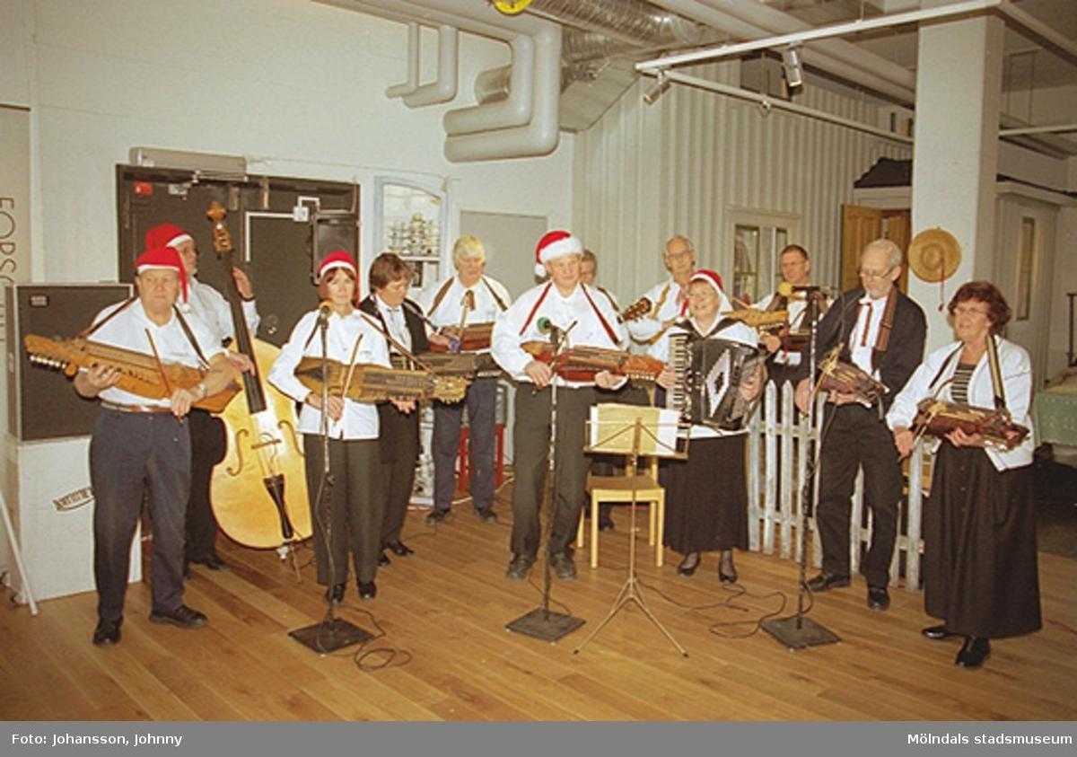 Lommebôs spelmanslag spelar i Forscaféet på Mölndals museum 2002-12-22. I mitten står museitekniker Sven-Åke Svensson och spelar nyckelharpa. Relaterade motiv: 2002_1163 - 1170.
