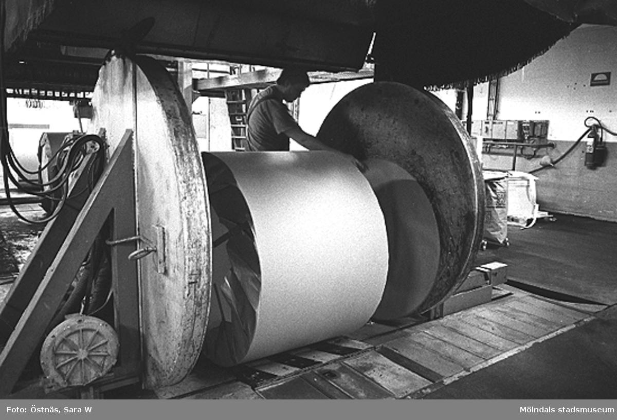Stefan Roslund i arbete med rullpackning. Först har rullen gått ett antal varv i grovt vattenbeständigt om- slagspapper innan sidorna limmas på. Bilden ingår i en serie från produktion och interiör på pappersindustrin Papyrus.