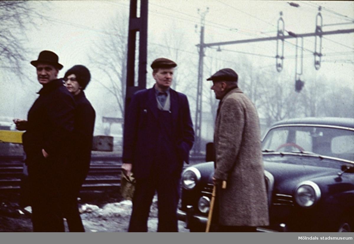 """""""Pilo"""" samtalar med några personer vid ett järnvägsspår i Mölndal, år 1965. Originalet """"Pilo"""" var mjölkutkörare med häst och senare med bil hos """"Mjölkekarlssons"""" på Frölundagatan 6. Det var han som hade """"mjök i kängera"""" enär han hade dåliga förvrängda fotsulor. Men han var en glad """"skit""""."""