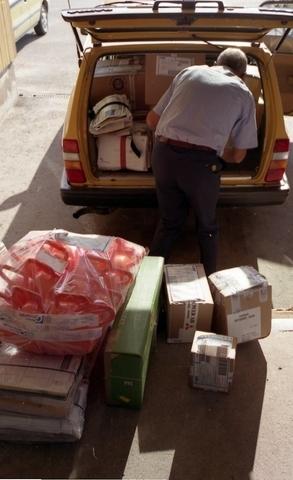 Lantbrevbärare Reinhold Andersson paketerar utgående post i postbil vid en postanstalts lastkaj. Tillhör en dokumentation av en lantbrevbärare i trakten av Valdermarsvik av fotograf Ove Kaneberg.
