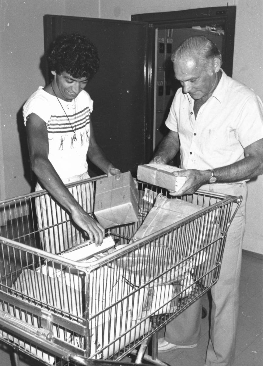 Postkassörselev Hassan Esteka och postmästare Gösta Eriksson hjälps åt på postkontoret Spånga 4, 1982.